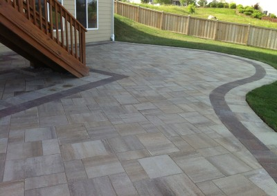 Natural Stone Paver Patio Around Deck Stairs